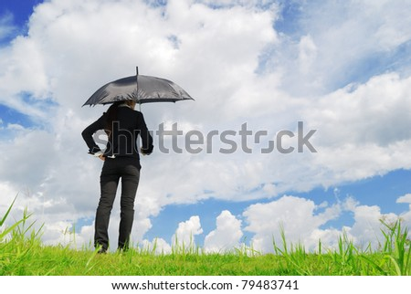 Business woman holding black umbrella in grassland blue sky - stock photo
