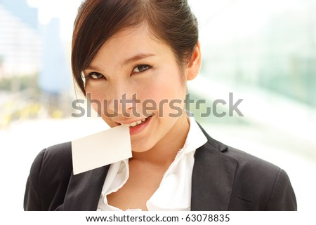 Business woman holding business card in her teeth