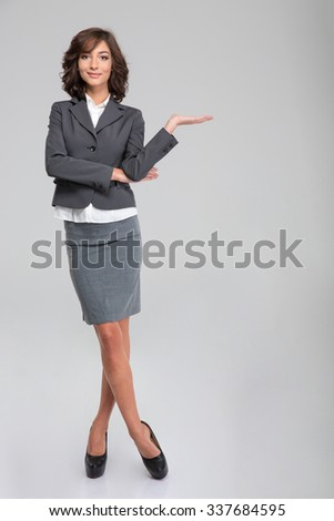 Business woman holding copyspace on palm over white background - stock photo