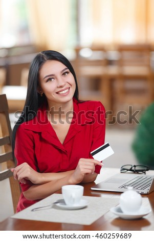 Business woman holding credit card and looking at the camera. Woman pays for a purchase with credit card. Purchase on the Internet. Buy online. Shopping online
