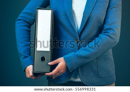 Business woman holding document binder with archived paperwork and other corporate legal sheets