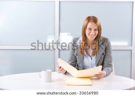 Business woman holding legal documents in modern office - stock photo