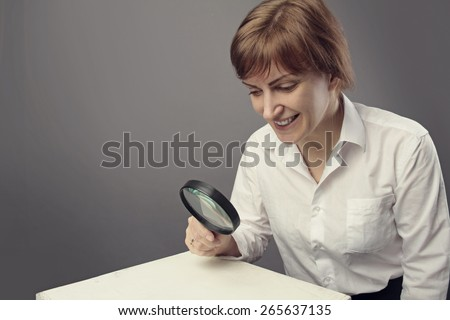 business woman holding magnifying glass - stock photo