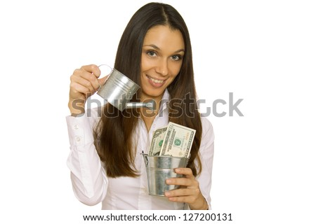 Business woman holding money in a bucket and a watering can. Isolated - stock photo