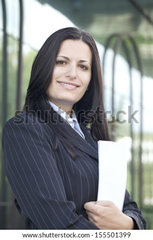Business woman holding papers outdoors