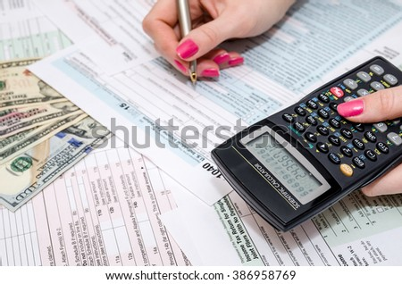 business woman holding pen and calculator on Tax  Form 1040 - stock photo