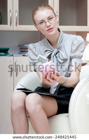 Business woman  holding piggy bank containing one dollar.
