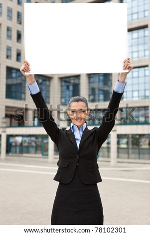 business woman holding raised banner in front of office buildings - stock photo