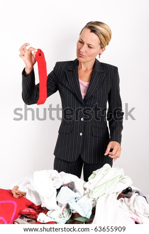 Business woman holding red sock while laundering - stock photo