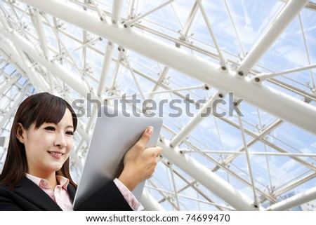 Business woman holding tablet pc in the modern office - stock photo