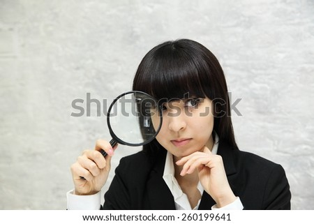 Business woman holds a magnifying glass