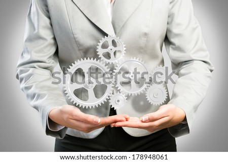 business woman holds up a mechanism of gears, concept of ready solutions - stock photo