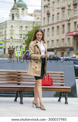 Business woman in a beige raincoat holding a tablet in the summer city - stock photo