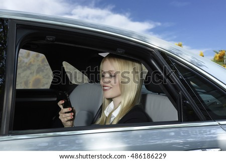 Business Woman in a car talking on her mobile phone with a field of sun flowers in the background