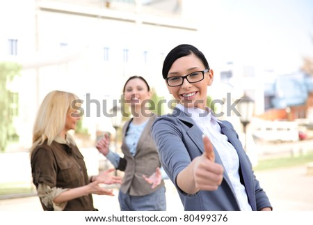 Business woman in a friendly environment of her colleagues standing outdoor and thumbs up with two of her partners at the back - stock photo