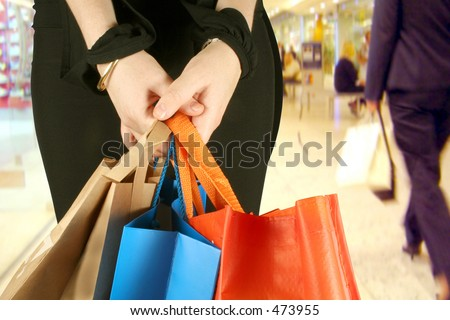business woman in a shopping centre with some bags - stock photo