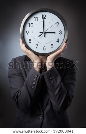 Business woman in a suit holding a large round numerical clock in front of her face, shot on a white background
