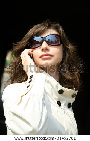 Business woman in a white coat is talking on the phone - stock photo