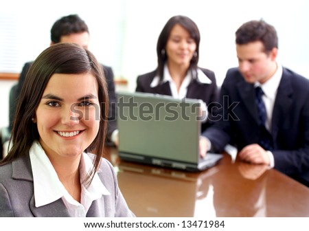 business woman in an office environment with people working behind her