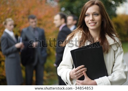 Business woman in an outdoor environment with her colleagues on the background - stock photo
