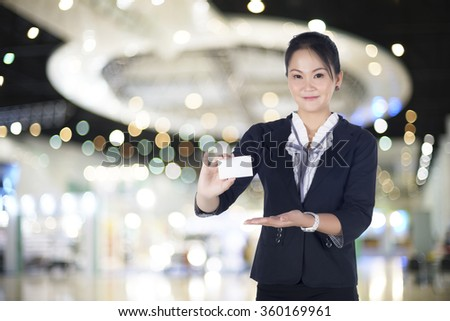 Business woman in black suit handing a blank business card,  Model is Asian woman. - stock photo