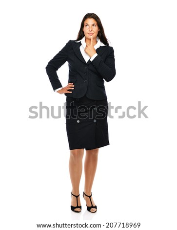 Business woman in black suit standing looking up, thinks about something.   Isolated on a white background.