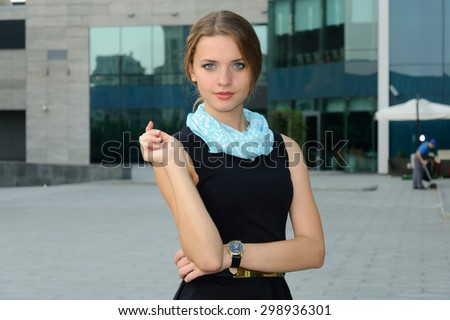 Business woman in formal attire is standing against the facade of a modern building - stock photo