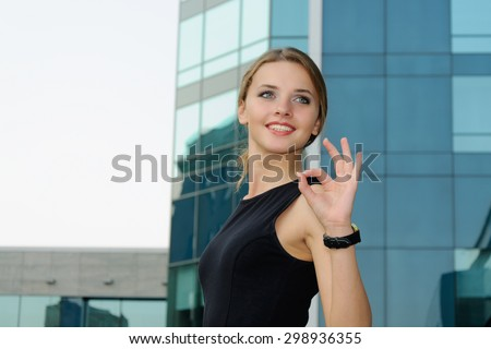 Business woman in formal clothes shows gesture ok against the facade of a modern building - stock photo