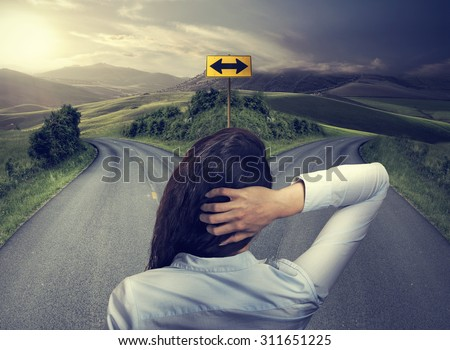 business woman in front of two roads thinking deciding hoping for best taking chance - stock photo