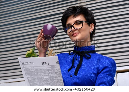 Business woman in glasses drink coffee and read newspapper - stock photo