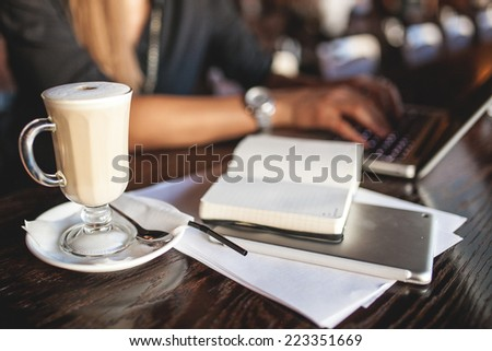 Business woman in glasses indoor with coffee and laptop taking notes in restaurant - stock photo