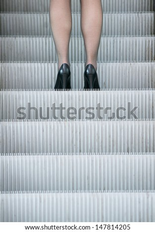 Business woman in high heels standing on escalator outdoors - stock photo