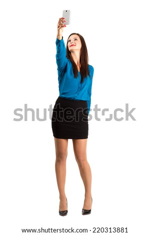 Business woman in high heels taking high angle selfie with one hand. Full body length isolated over white background. - stock photo