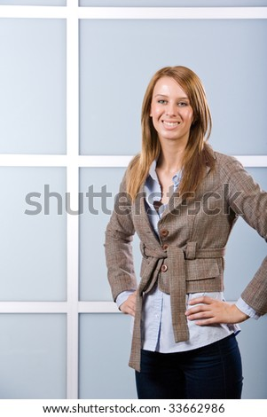 Business woman in modern office hand on hip - stock photo