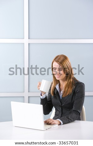 Business woman in modern office with laptop and coffee - stock photo