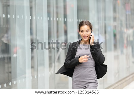 Business woman in motion, talking on mobile smart phone running outside on Manhattan, New York City. Beautiful young professional businesswoman. Multiethnic Asian Chinese and Caucasian ethnicity. - stock photo