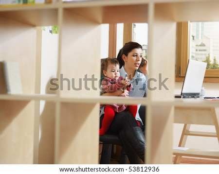 business woman in office, holding her little girl while talking on mobile phone. Viewed through library. Horizontal shape, full length - stock photo