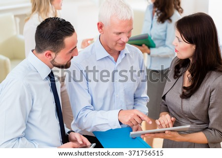 Business woman in office showing boss presentation, more business people standing in the background - stock photo