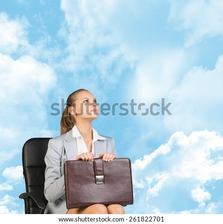 Business woman in skirt, blouse and jacket, sitting on chair and holding briefcase. Against background of blue sky and clouds - stock photo