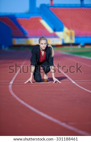 business woman in start position ready to run and sprint on athletics racing track - stock photo