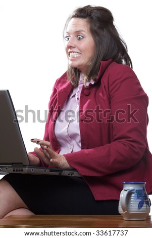Business woman in state of shock while using her laptop computer; isolated on a white background - stock photo