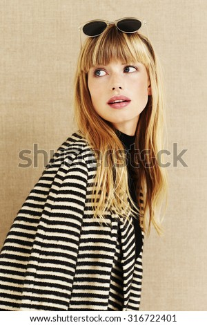 Business woman in striped coat looking over shoulder - stock photo