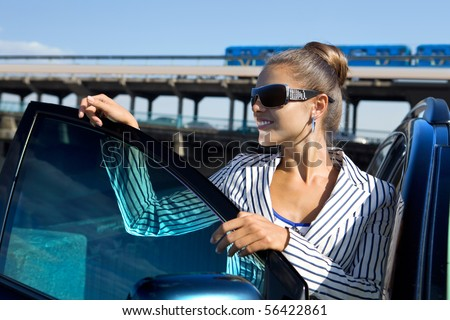 business woman in sunglasses near the car against city bridge