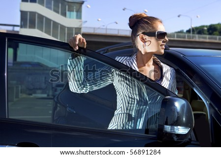 business woman in sunglasses near the car against city bridge - stock photo