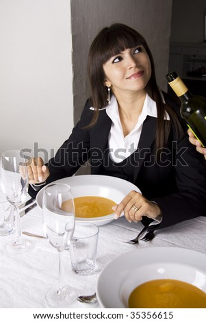Business woman is having lobster soup and white wine at a fine restaurant