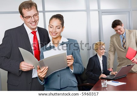 Business woman is showing her successful business plan to a colleague in the office on the background of two business people - stock photo