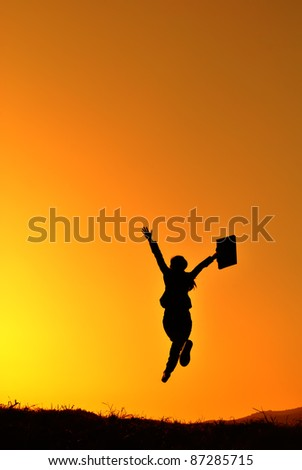 Business woman jumping and sunset silhouette - stock photo