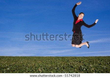 Business woman jumping on a green hillside