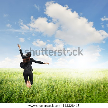 Business woman jumping to clouds sky in grassland - stock photo
