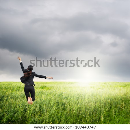 Business woman jumping to raincloud in grassland - stock photo
